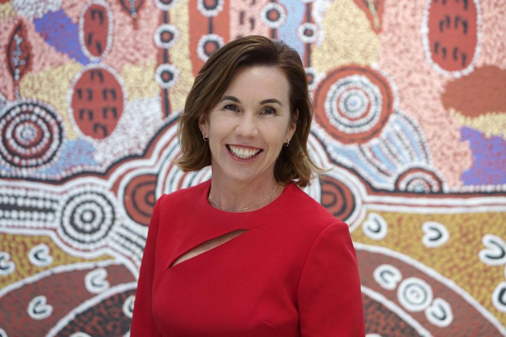 Uniting WA CEO, Amanda Hunt posing in front of Aboriginal reconciliation painting