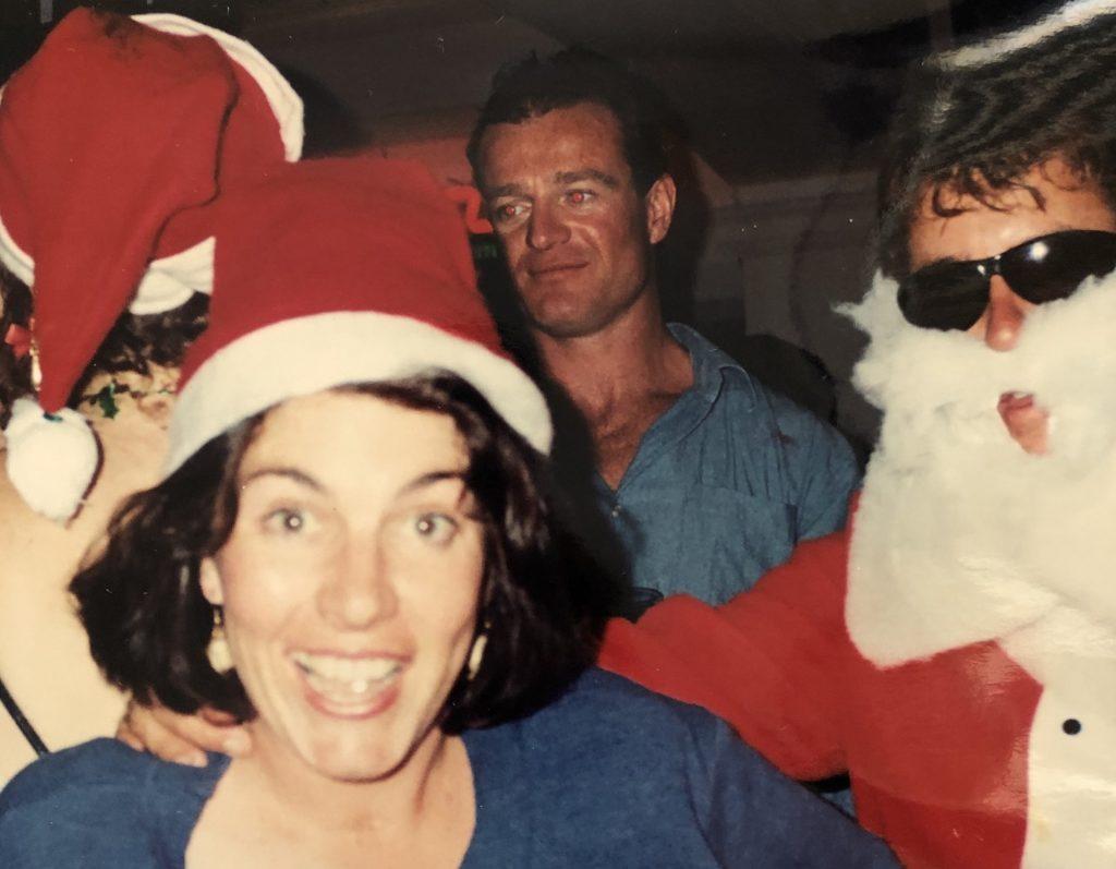 Jacinta grinning at camera while wearing a santa hat, at a Christmas party