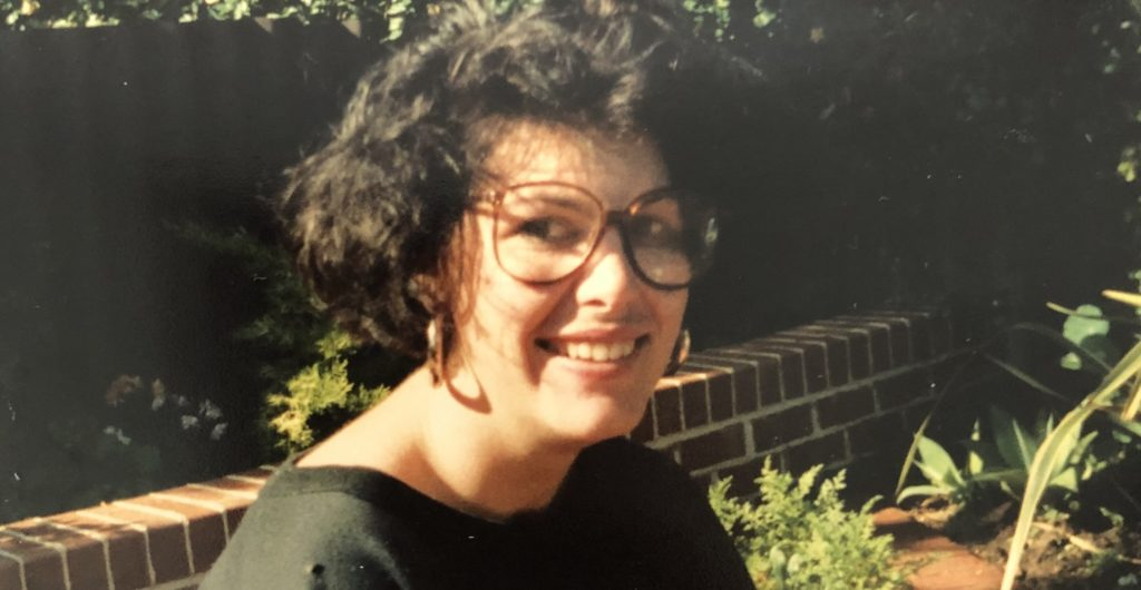 Close up of Jacinta smiling at camera after her accident, wearing glasses