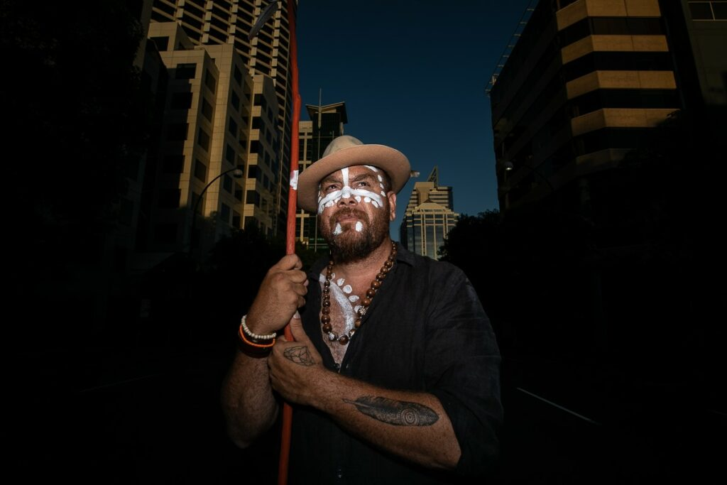 Image of Aboriginal artist, Tee Jay Worrigal. Tee Jay is holding a stick and wearing paint on his face as he stands on St Georges terrace