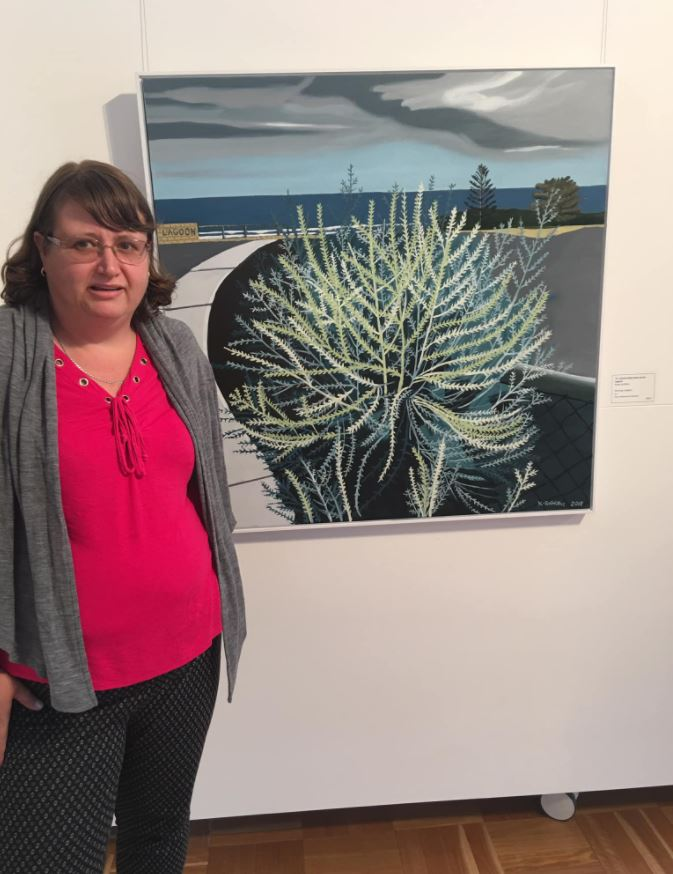 Kirsty standing next to one of her paintings in an exhibition